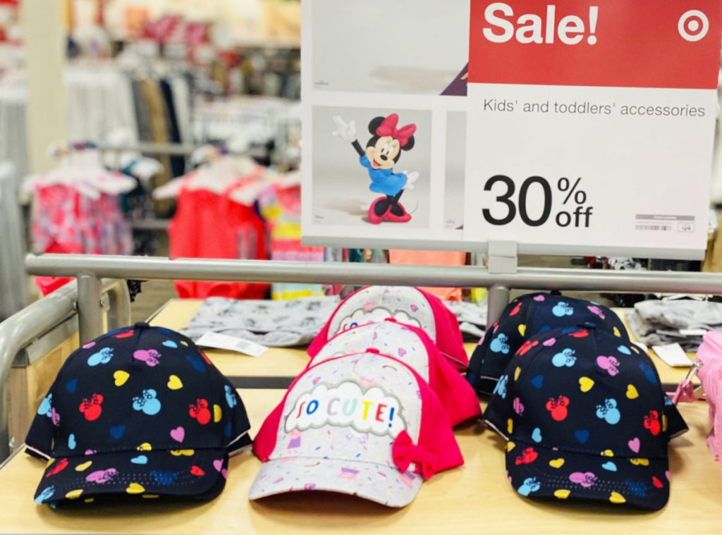 girls disney themed baseball hats on display shelf with 30% off sale sign at target