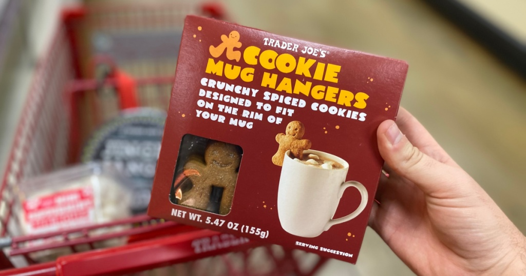 hand holding box of cookie mug hangers in front of cart full of items in store