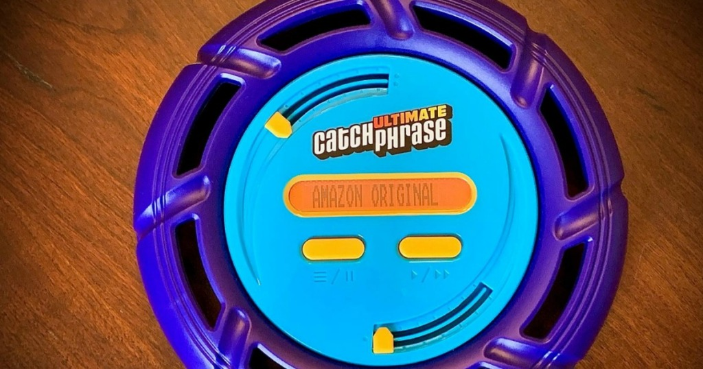 Ultimate Catch Phrase Electronic Party Game n a wooden surface