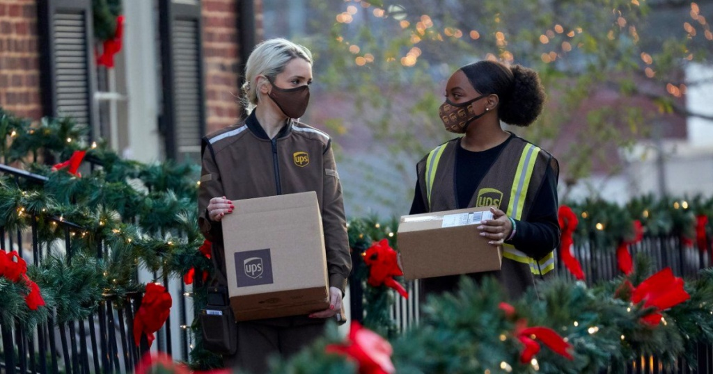 2 woman working for ups standing outside holding packages