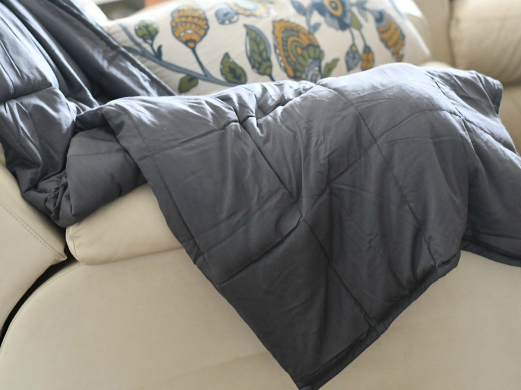 grey weighted blanket on a couch