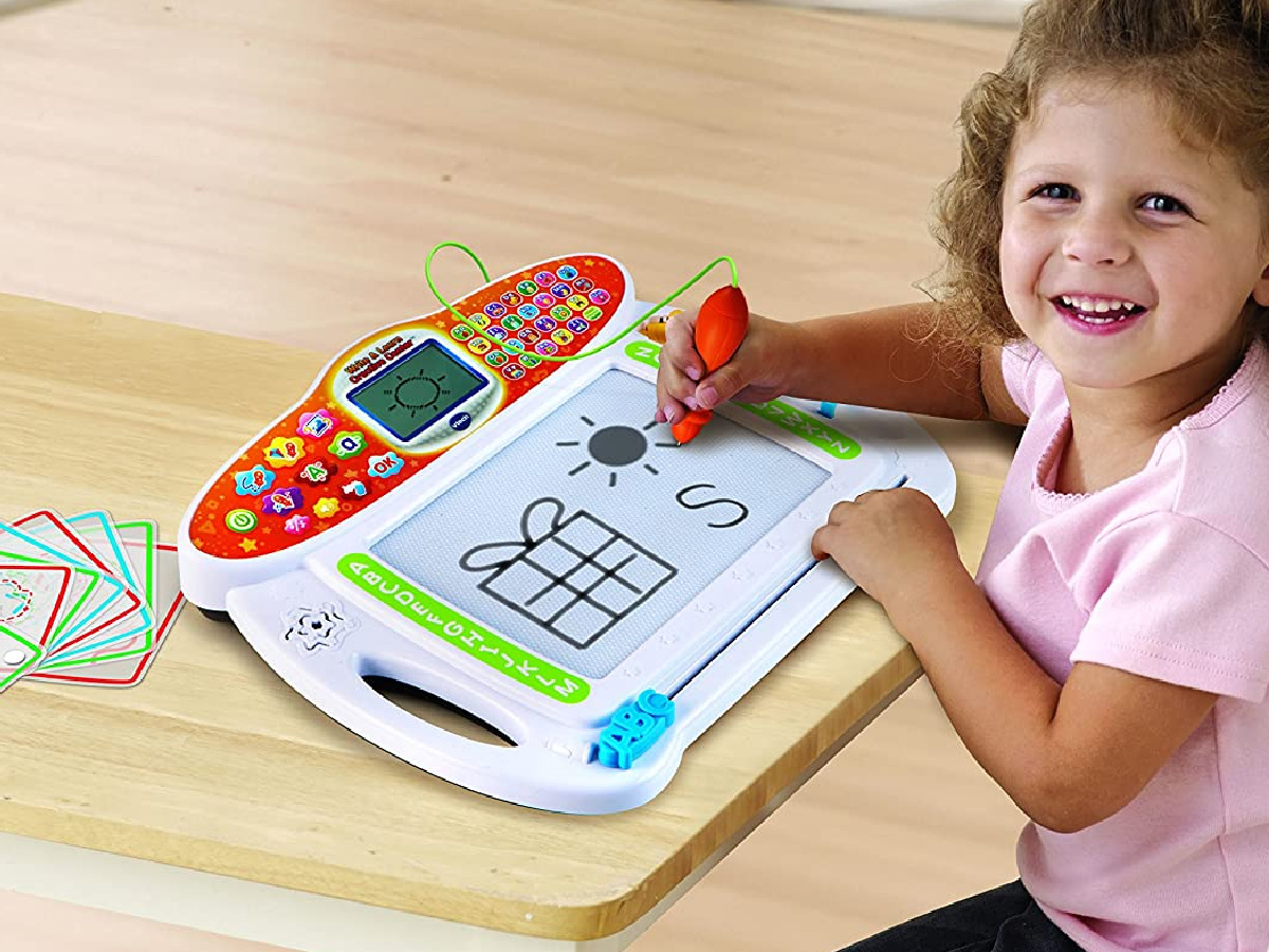 girl playing with writing toy on table