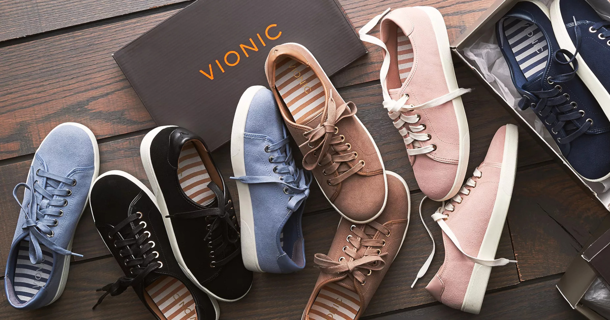 pairs of Vionic shoes strewn across a wooden surface