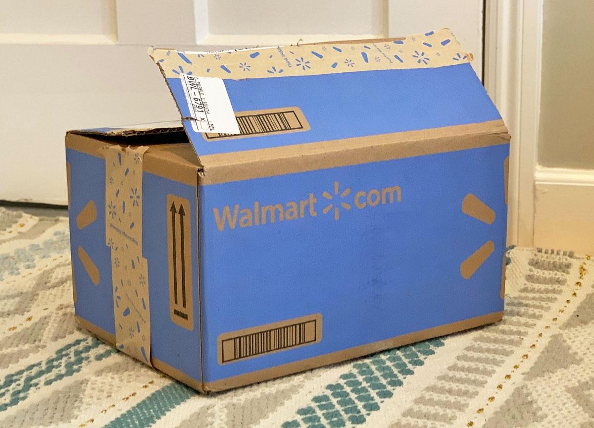 blue walmart.com shipping box on area rug near a door