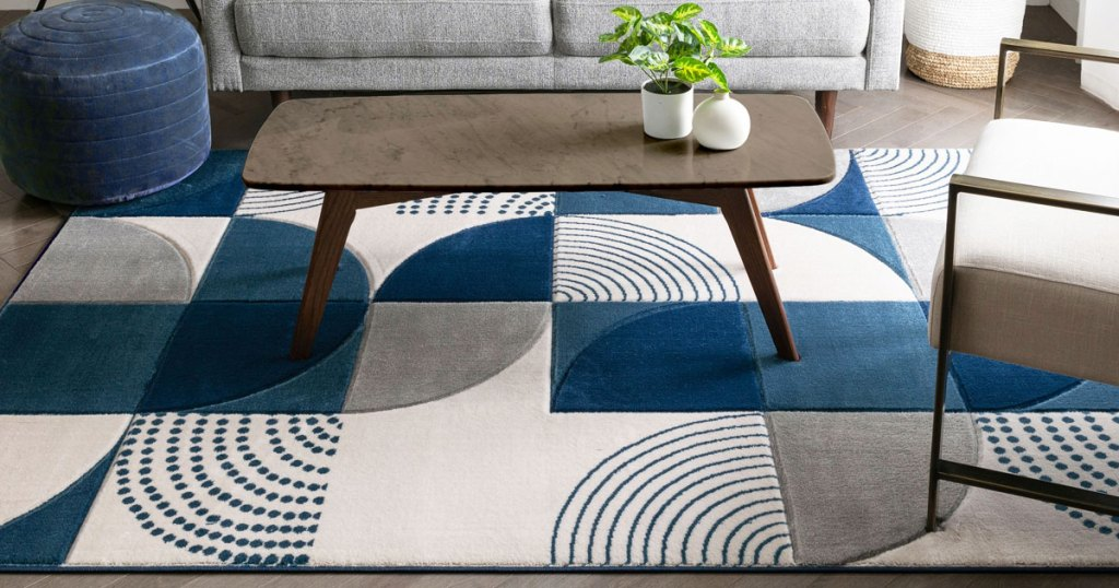 blue, grey, and white geometric print area rug on floor under a coffee table