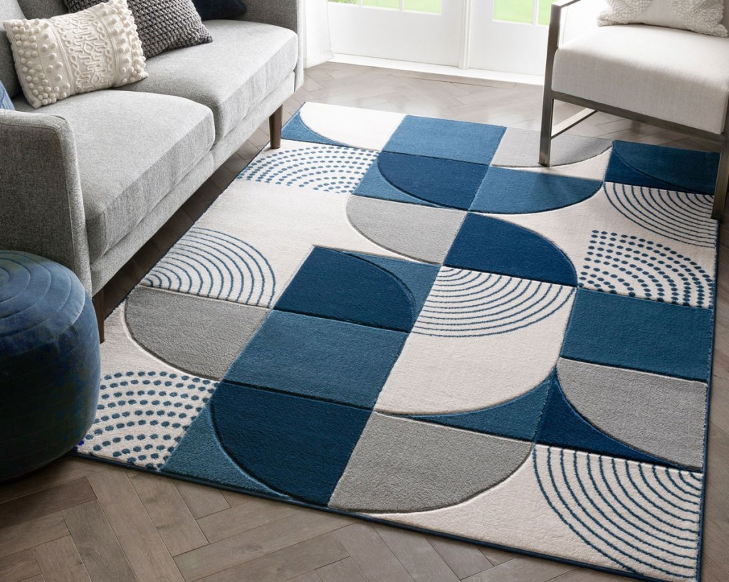 blue, grey, and white geometric print area rug on floor under an accent chair and grey couch