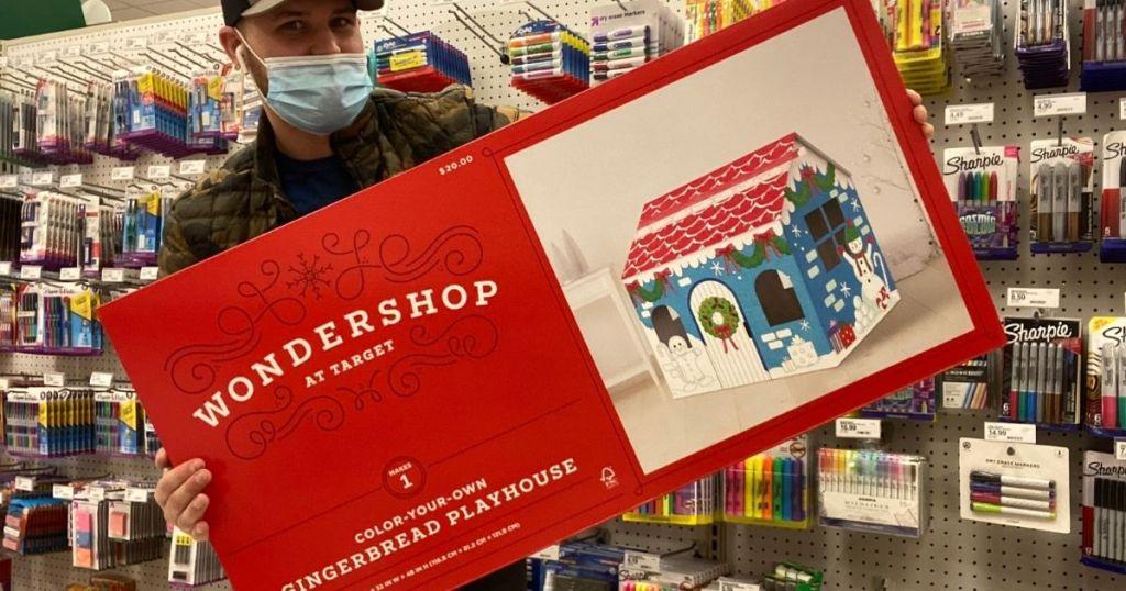 man holding Wondershop Gingerbread Playhouse