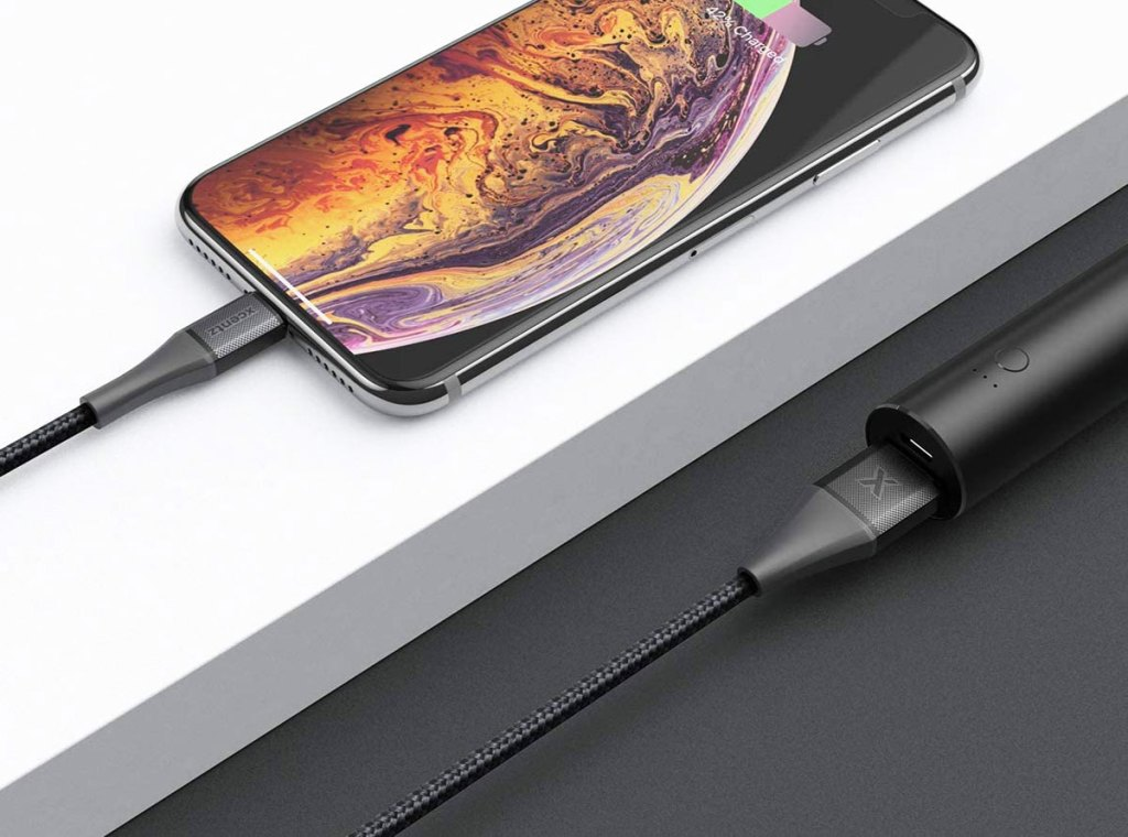 iphone with black braided charging cable plugged into it and a black power bank
