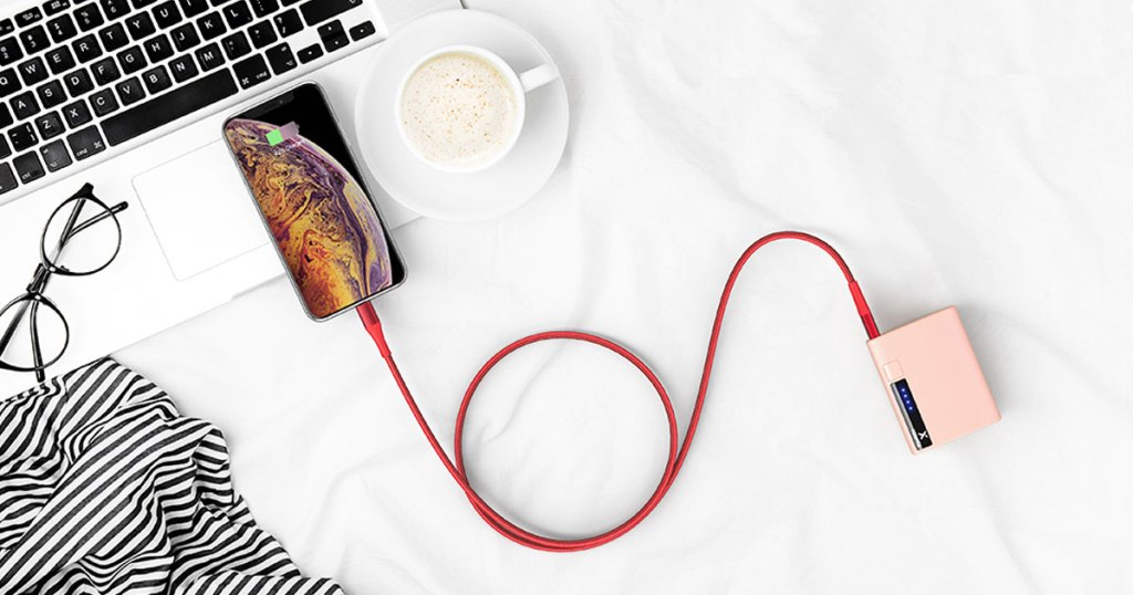 iphone plugged into a pink power bank by a red braided charging cable