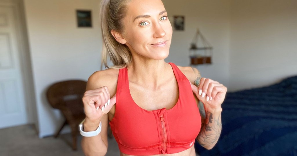 woman with blonde hair standing in a bedroom with her thumbs under the straps of her orange zip-front sports bra