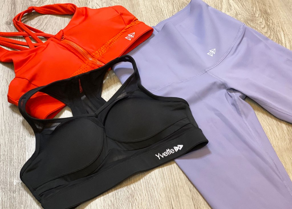 pair of light purple leggings, an orange sports bra, and a black sports bra all laid out on a wood floor