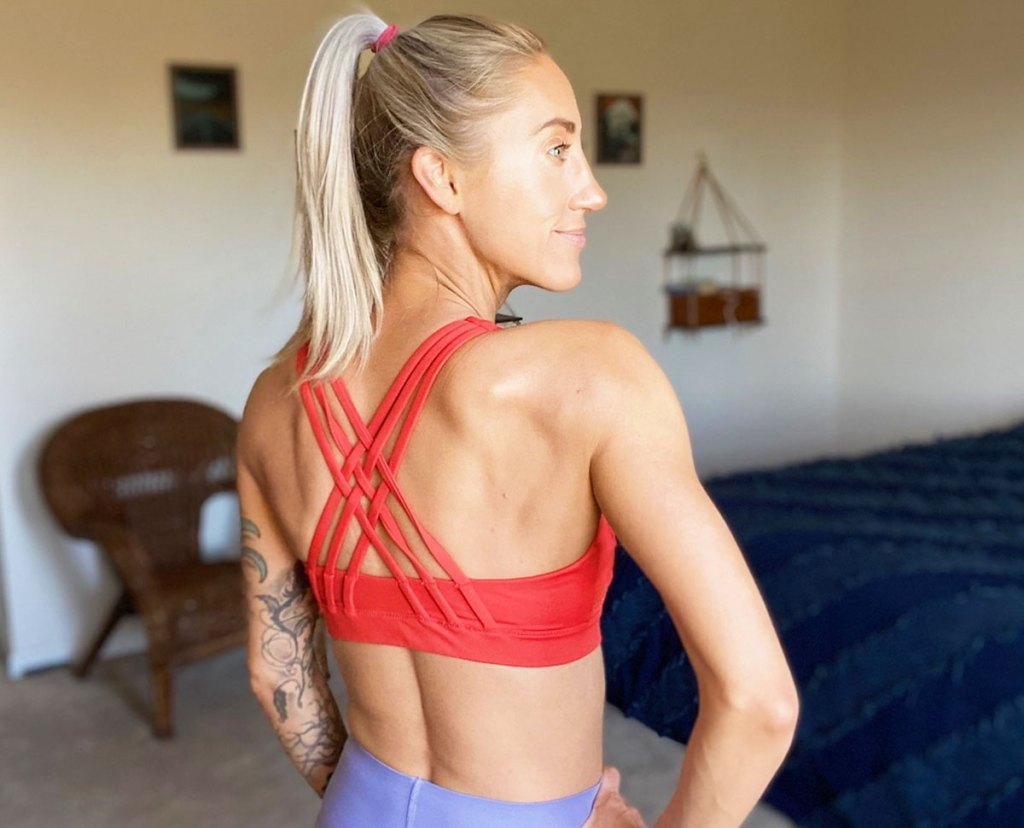 woman standing in bedroom showing the back criss-cross straps on the back of her orange sports bra