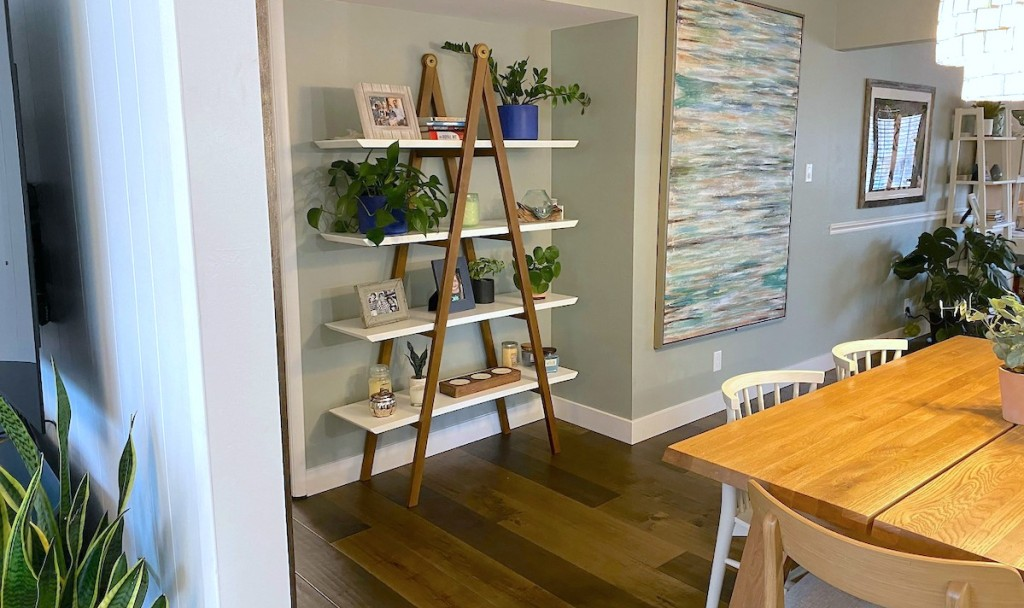 a frame article shelf sitting on wood floor in dining room with various decor