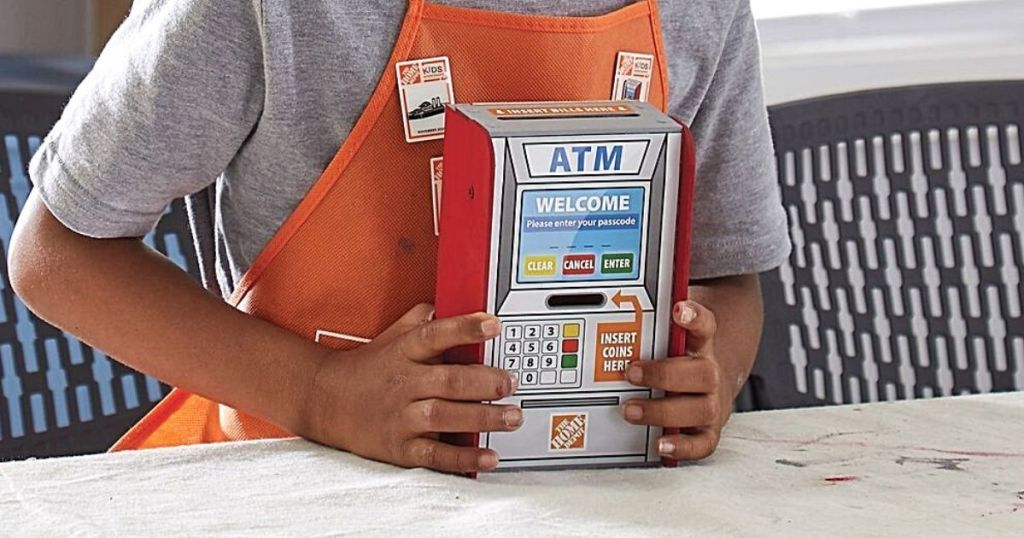 kid wearing Home Depot apron and holding ATM kit