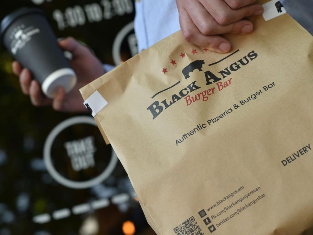 holding Black Angus takeout bag
