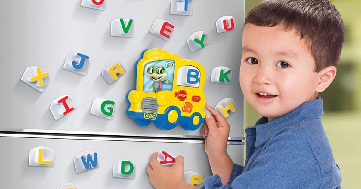 boy using magnetic letters on refrigerators