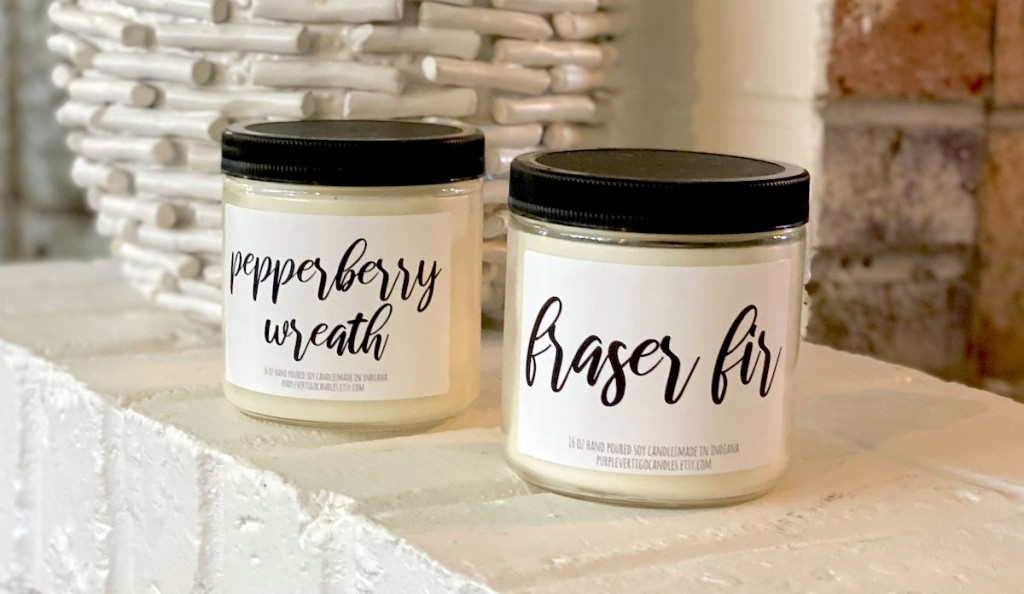 two candles from subscription box on white fireplace
