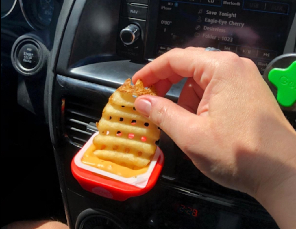 hand dipping waffle fry into dip clip