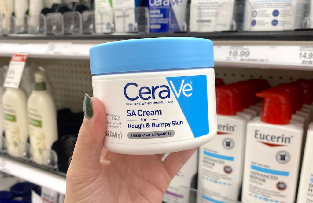 hand holding a tub of cerave cream in store aisle