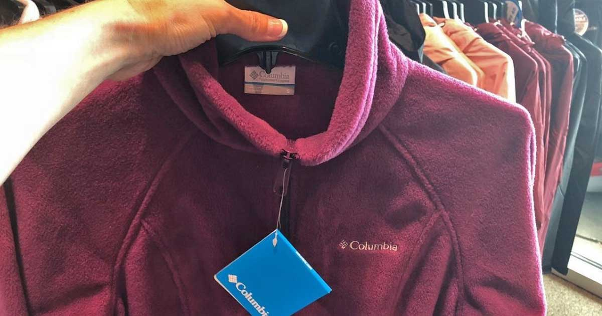 person holding up purple columbia jacket on hanger