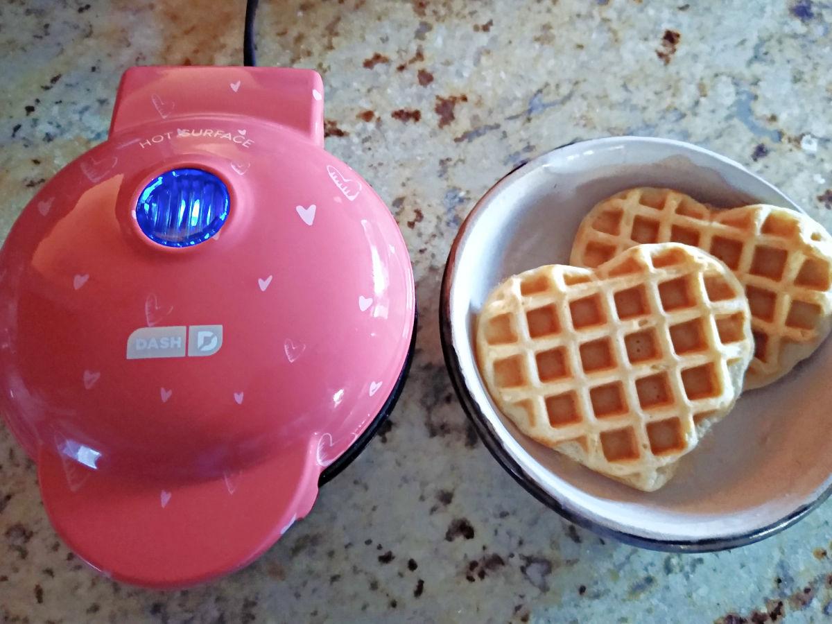 heart-shaped waffles next to mini waffle maker