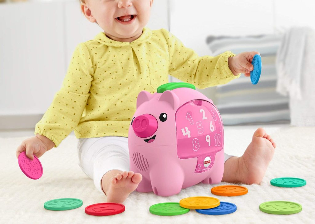 baby playing with fisher price piggy bank