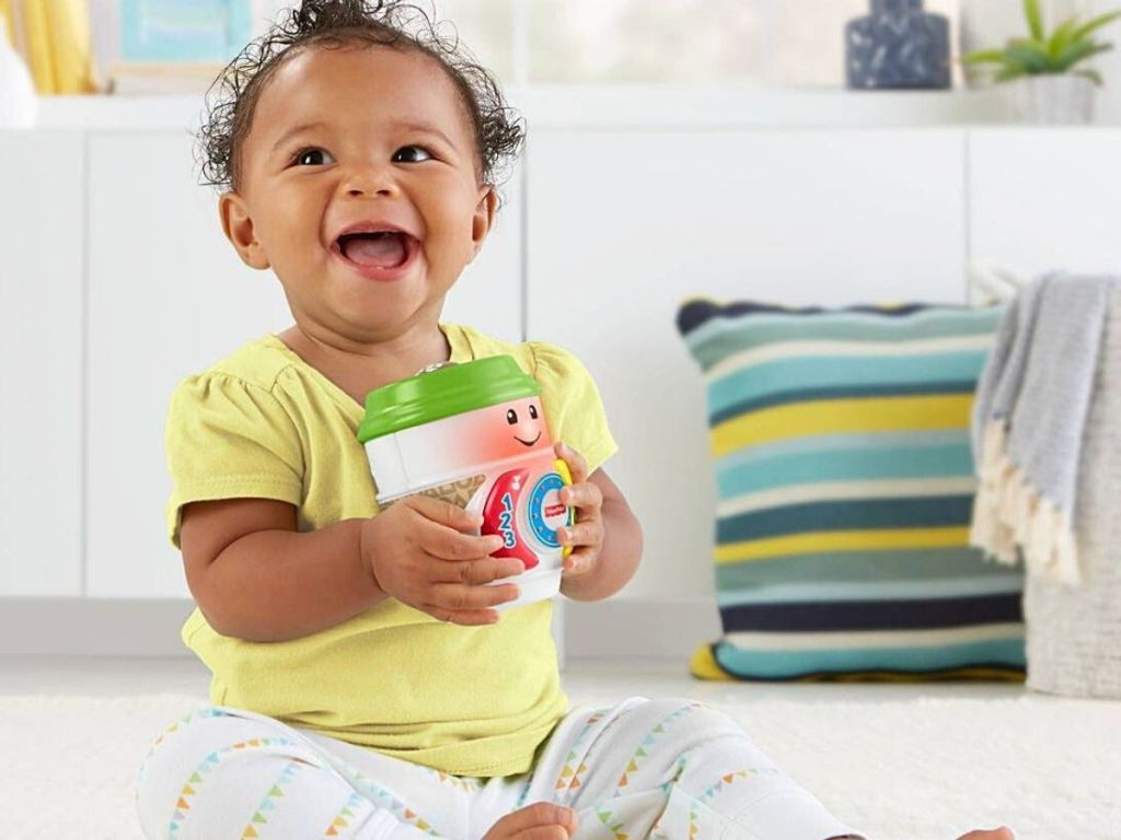 baby holding Fisher-Price coffee cup