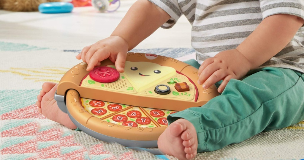 little boy playing with fisher price pizza