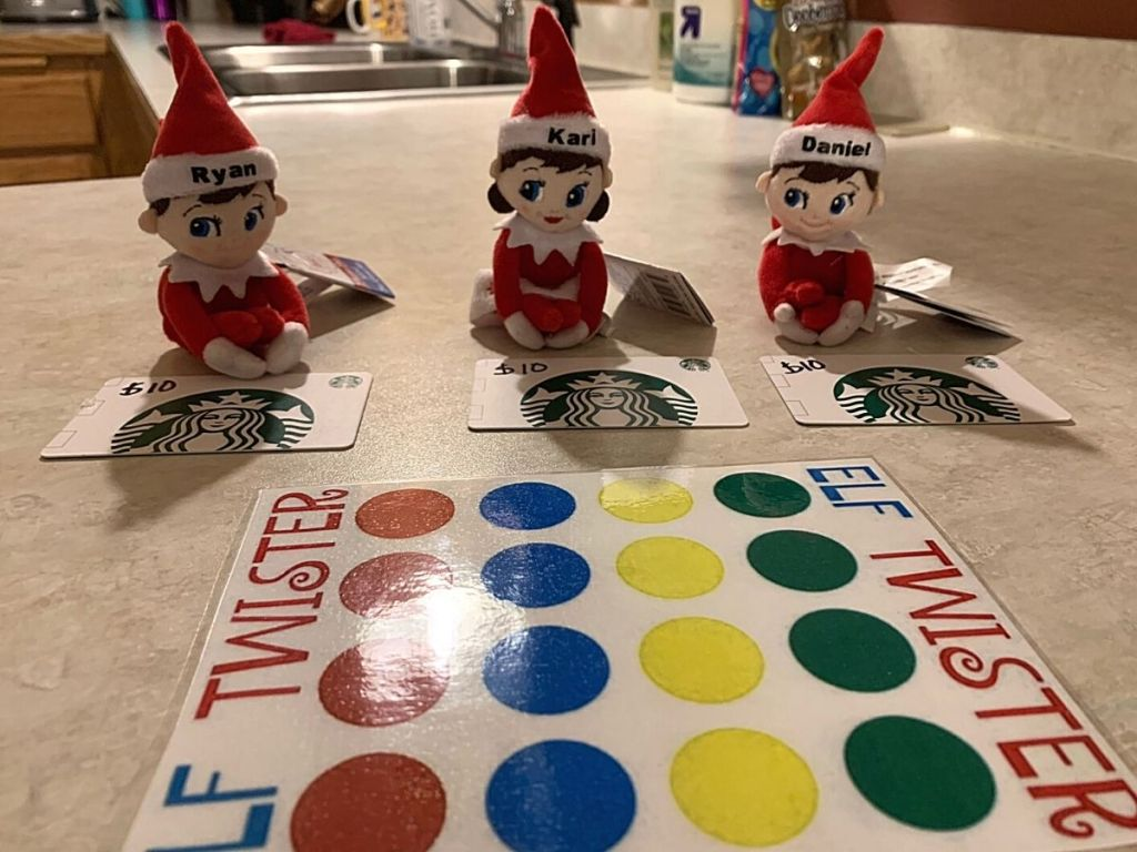 three elves in front of Starbucks gift cards sitting by Elf twister game