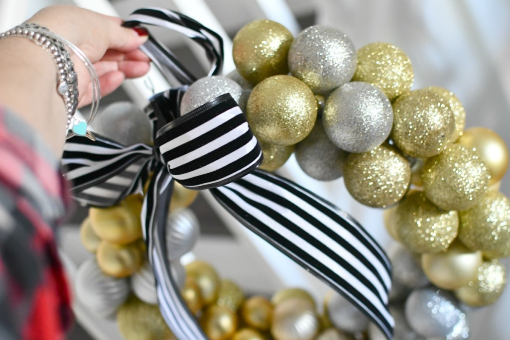 holding a ball ornament wreath with black and white ribbon