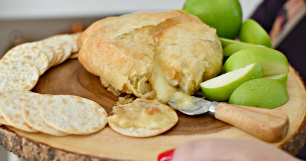 holding a tray with melted puff pastry baked brie