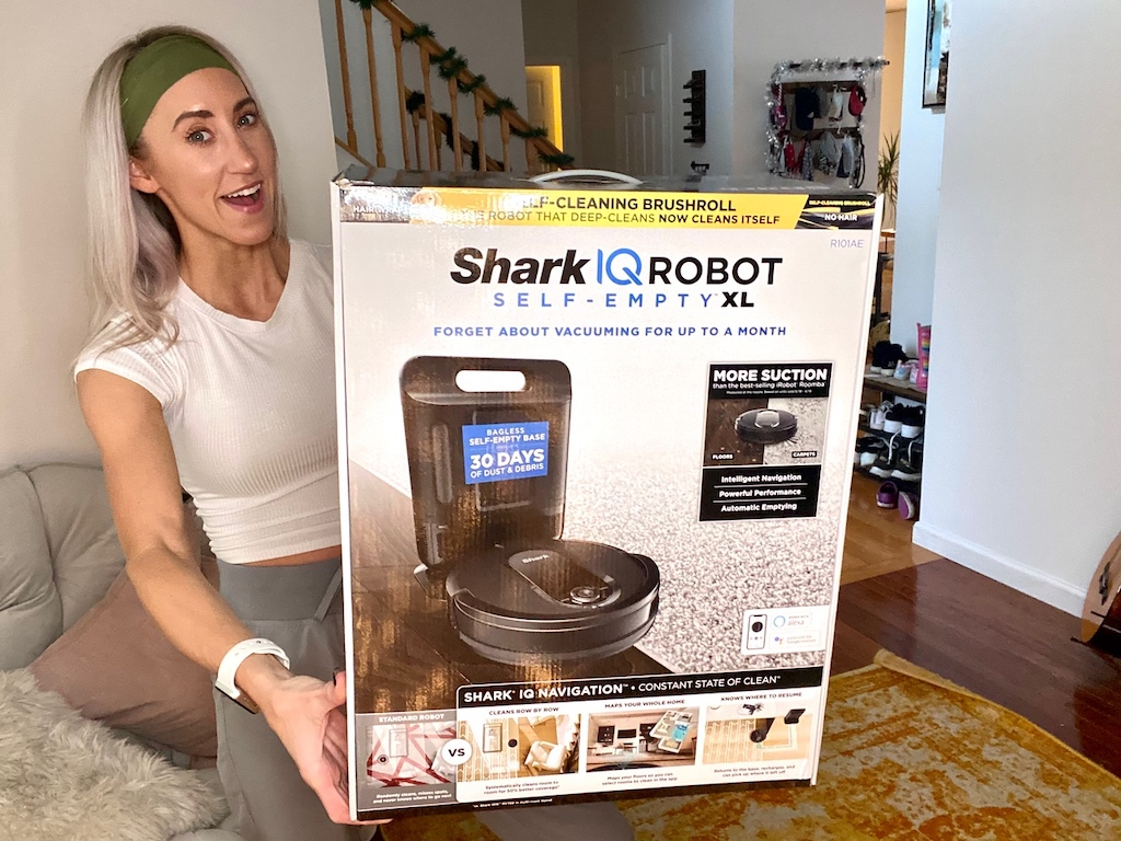 holding large Shark IQ Robot vacuum large box
