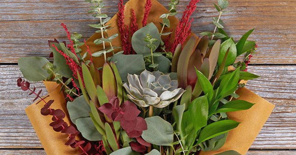 Succulent holiday bouquet with reds and greens. Close up of the top of the bouquet laying on a wooden background.