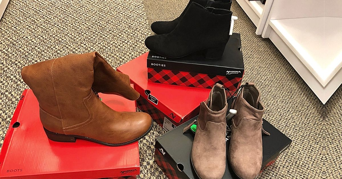 three pairs of womens boots sitting on boxes in a store