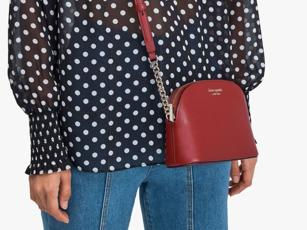 woman wearing polka dot shirt and red kate spade bag