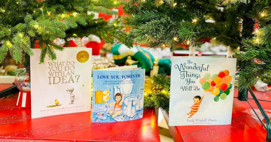 row of the best kids gift books sitting under lighted christmas trees