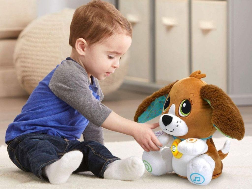 boy playing with dog stuffed animal