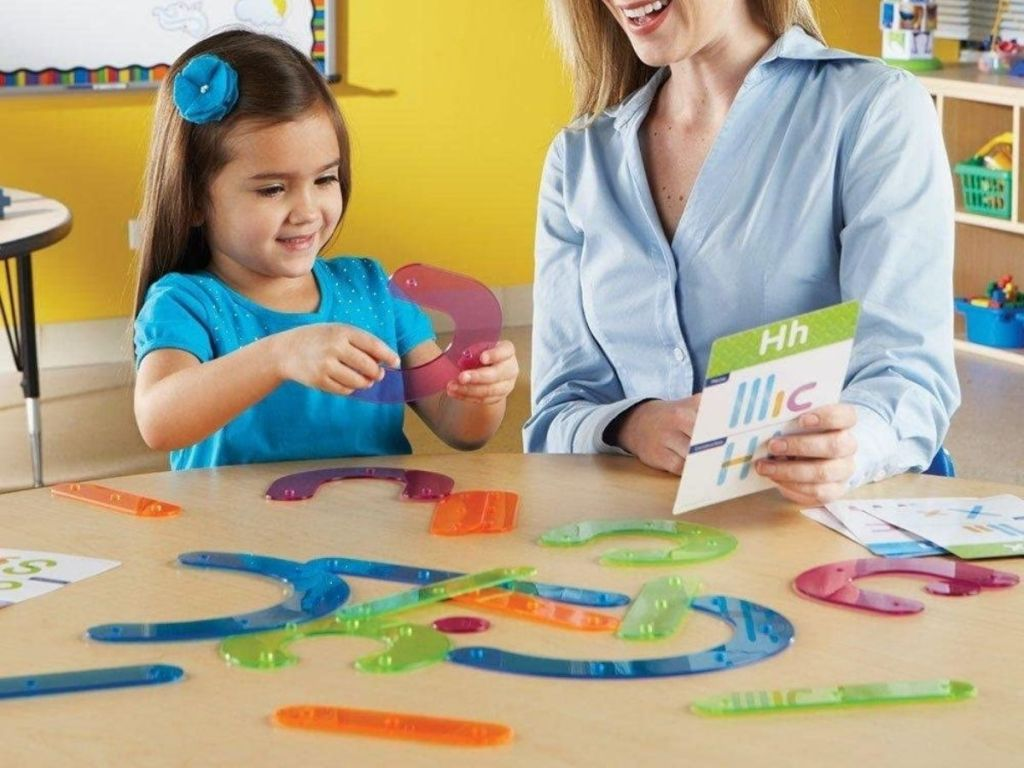 woman and daughter using letter construction set