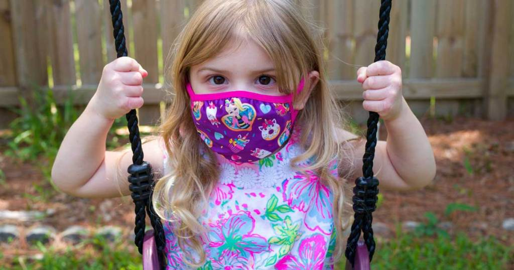 little girl on swing wearing a face mask