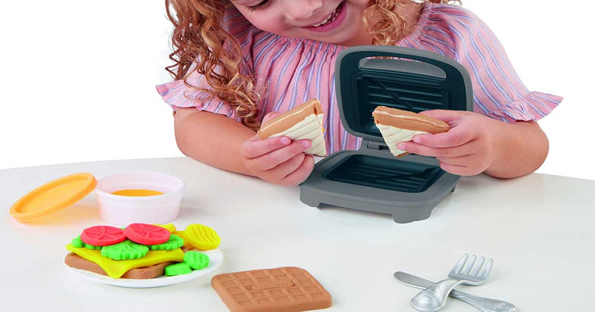 little girl playing with a cheese sandwich maker