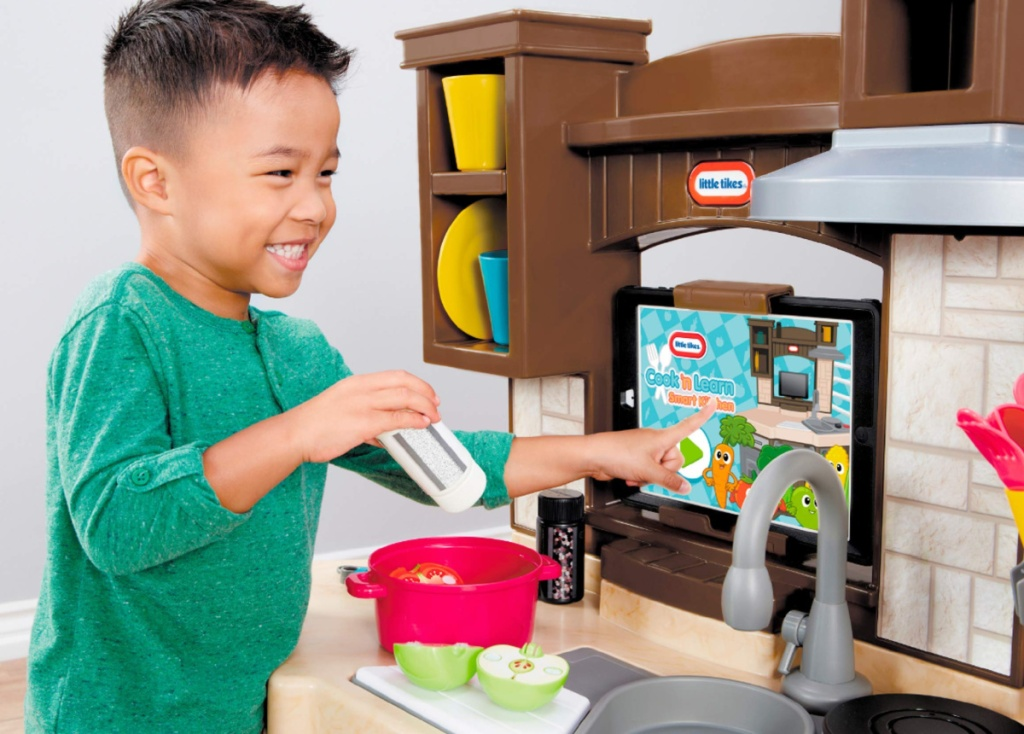 boy playing with little tikes kitchen