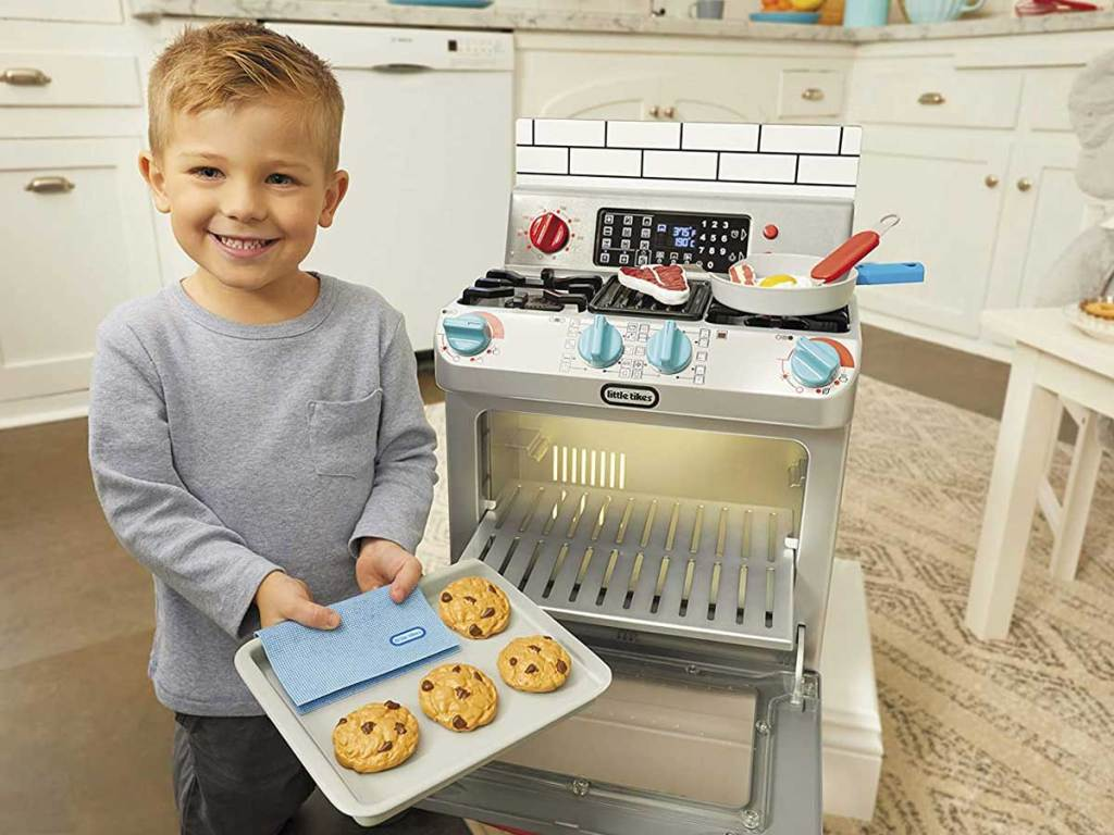 little boy playing with toy oven