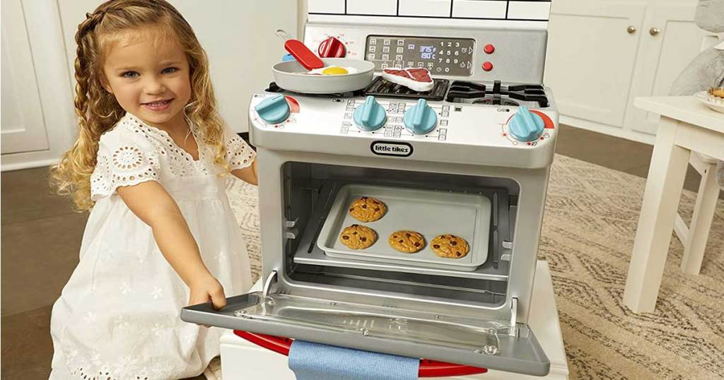 little girl playing with toy oven