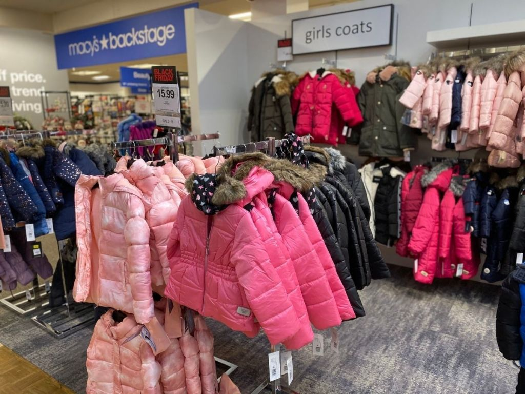 kids puffer coats hanging in store