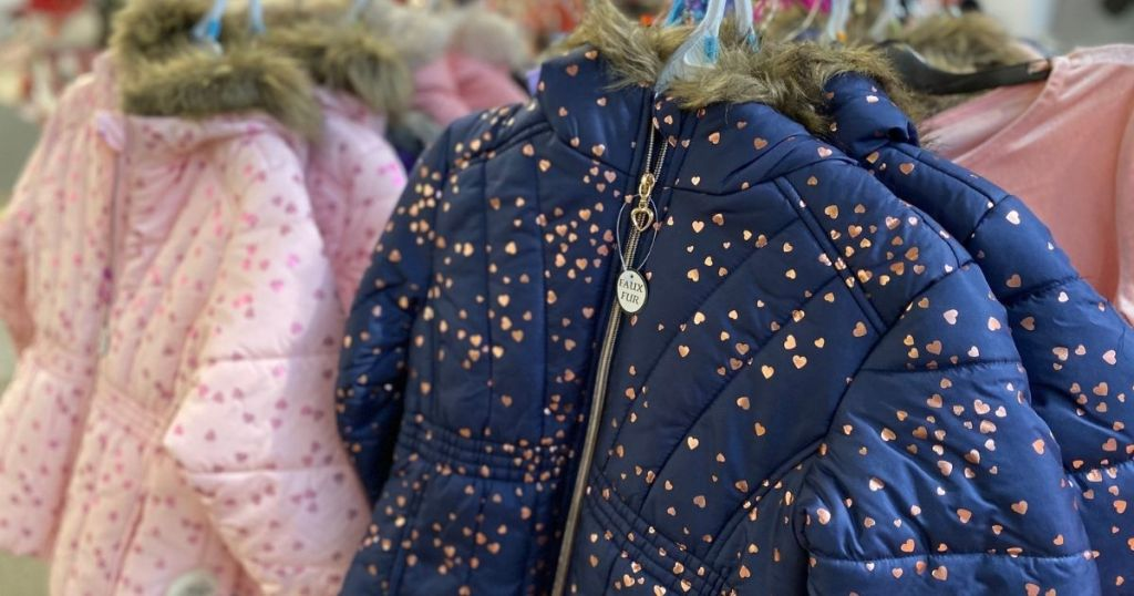 blue puffer kids coat with gold hearts hanging in store