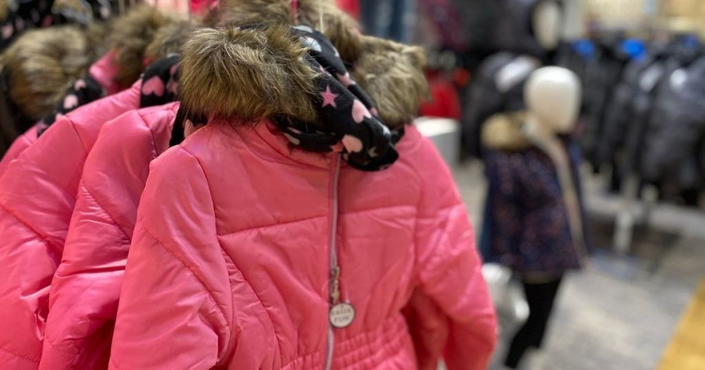 pink puffer coat with scarf hanging in store
