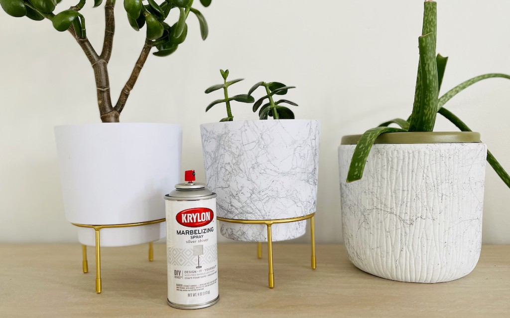 three white and marble planters sitting on table with marble spray paint