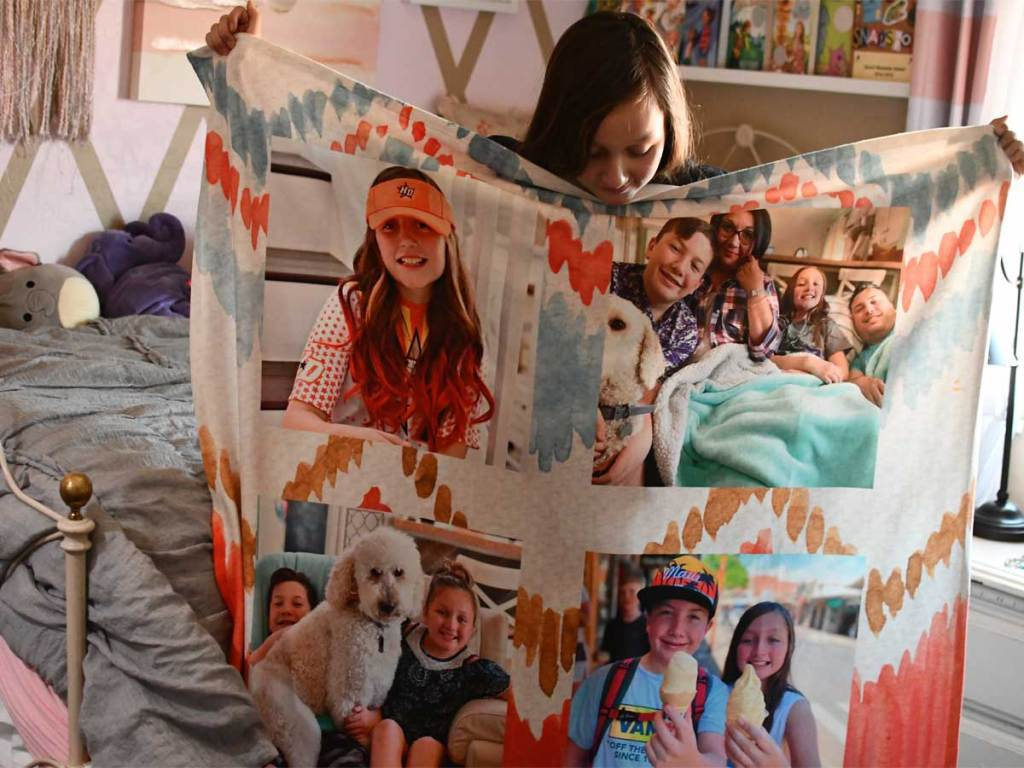girl holding up a photo personalized blanket