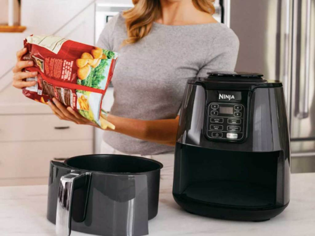 woman putting chicken nuggets into air fryer