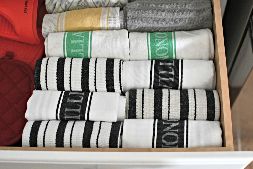 organizing kitchen towels by rolling them